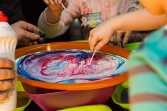 Barn experimenterar med färgerna i disken Royaltyfri Fotografi