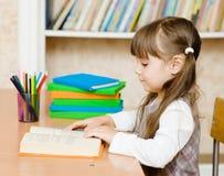 barn för bokavläsningsschoolgirl Arkivbild