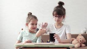 Barn för ett kemiskt experiment och förvånas av den kemiska reaktionen två små flickor som hemma spelar in stock video