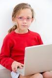 barn för flickabärbar datorstående Arkivbilder