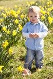 barn för jakt för fält för pojkepåskliljaeaster ägg fotografering för bildbyråer