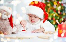 Barn, för jul skrivar ett brev till jultomten Arkivbilder