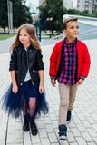 Barn för modemodeller går trappan av stadsgatorna En pojke och en flicka, en blå kjol Royaltyfri Foto