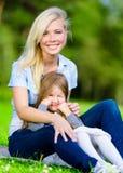 barn för solnedgång för dottergräsmoder sittande fotografering för bildbyråer