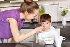 Barn familj och ätabegrepp Ståenden av den förtjusta unga gulliga kvinnlign matar hennes stiliga lilla unge med läckra sädesslag Arkivbild