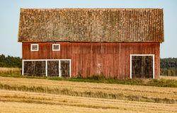 Barn in a field after harvest. A red barn in a field after harvest Stock Photos