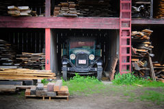 Barn Find. Mystic, USA - 28 May 2011: Vintage 1929 Ford truck in storage in weathered, overgrown lumber yard Stock Photos