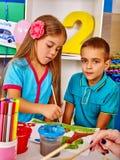 Barn flicka och pojke med borstemålning i grundskola för barn mellan 5 och 11 år Arkivfoto