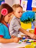 Barn flicka och pojke med borstemålning i grundskola för barn mellan 5 och 11 år Royaltyfri Fotografi