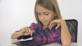 Barn flicka som spelar minnestavlan, dator som surfar internet, kontor för liten unge royaltyfri fotografi