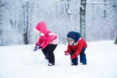 Barn formar snögubben Arkivfoton