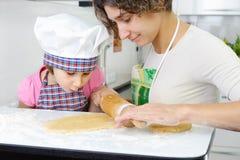 Barn fostrar med lite dottern som förbereder kakor arkivfoto