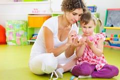 Barn fostrar och ägg för dottermålningpåsk Royaltyfri Fotografi