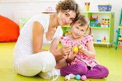 Barn fostrar och ägg för dottermålningpåsk royaltyfria bilder