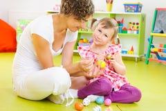 Barn fostrar och lite ägg för dottermålningpåsk arkivfoton