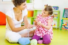 Barn fostrar och lite dottern som dekorerar påskägg Arkivbilder