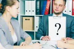 Barn frustrerat papper för visningen för affärsmannen täcker med frågefläcken till hans kollegor på meting för affär arkivfoton