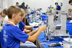 Barn gör en robot på robotolympiaden fotografering för bildbyråer