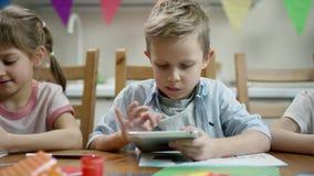 Barn gör förberedelsen för fiesta medan ett av dem lek i minnestavlan med den överskridna kameran stock video