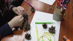 Barn gör hantverk från kottar arkivfilmer