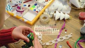 Barn gör hantverk och leksaker, julträdet och annat Målningvattenfärger Top beskådar Konstverkarbetsplats med idérik accessori lager videofilmer