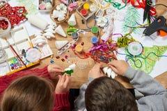 Barn gör hantverk och leksaker, julträdet och annat Målningvattenfärger Top beskådar Konstverkarbetsplats med idérik accessori royaltyfri bild