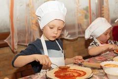 Barn gör pizza kock little arkivfoto