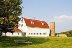 Barn with Gambrel Roof and Silo. Classic gambrel barn with silos on a sunny farm Stock Photography
