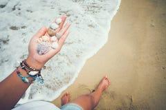 Barn garvade kvinnor räcker det hållande snäckskalet på den tropiska stranden i sommar Arkivfoto
