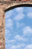 Barn gate door arch and sky, stone wall closeup, vertical bright white summer clouds cloudscape copy space background, plastered Stock Photography