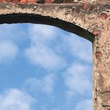 Barn gate door arch and sky, stone wall closeup, vertical bright white summer clouds cloudscape copy space background, plastered royalty free stock photos