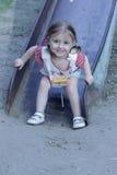 Barn glider ner nära huset eller i parkera Lycklig liten flicka 2-3 år som glids från glidbana Arkivfoton