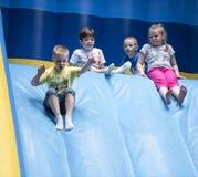 Barn glider ner uppblåsbara glidbanor på ett nöjesfält Arkivbild