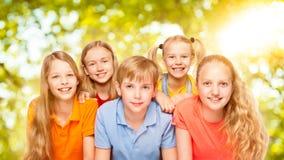 Barn grupperar fem personer, ungeflickor och pojkestående, elever Royaltyfri Fotografi