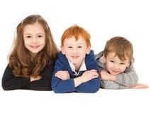 barn grupperar lyckligt läggande le arkivbilder