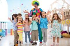 Barn grupperar med clownen som firar f?delsedagpartiet arkivfoto