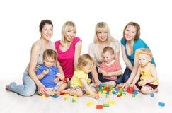 Barn grupperar med mödrar som spelar Toy Blocks Greve för små ungar Arkivfoton