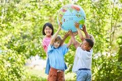 Barn grupperar, som ett lag rymmer ett jordklot arkivfoto