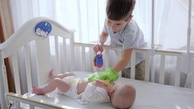Barn gyckel, unge med leksaken i armar roar med yngre bror i lathund nära fönster arkivfilmer
