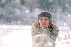 Barn härlig kvinna som blåser snow in mot kamera på vinterbakgrund Barn härlig kvinna som blåser snö in mot kamera på vinterbakgr royaltyfri foto