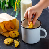 Barn handen för ` som s doppar ett kex i en kopp av, mjölkar Arkivfoto