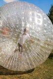 Barn har gyckel i den Zorbing bollen Arkivfoton