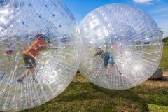 Barn har gyckel i den Zorbing bollen Fotografering för Bildbyråer