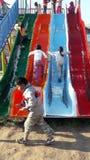 Barn har gyckel med en stor glidbana på en lekplats förutom Cuzco, Peru royaltyfria foton