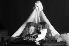 Barn har pajamapartiet Flickor med lyckliga framsidor ligger under filttältet Royaltyfri Bild