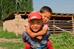 Barn har roligt utomhus- i central asiatisk by Arkivbild
