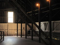Barn hayloft. With window that has light shining through onto the wooden floor and lights shine down from the rafters Royalty Free Stock Photo