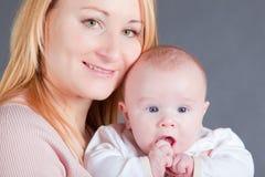 barn henne moderstående Arkivfoto