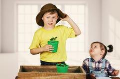 Barn hjälper deras föräldrar att att bry sig för växter Arkivfoto
