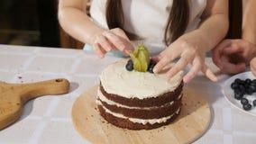 Barn hjälper deras mamma att dekorera den hemlagade kakan med blåbär och physalisen, handcloseup stock video
